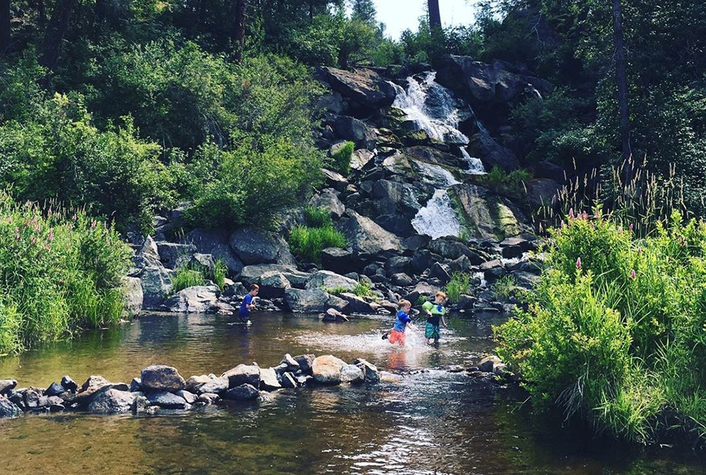 Children play at the base of the waterfall at Horseshoe lake. - HILLARY BERRY PHOTO