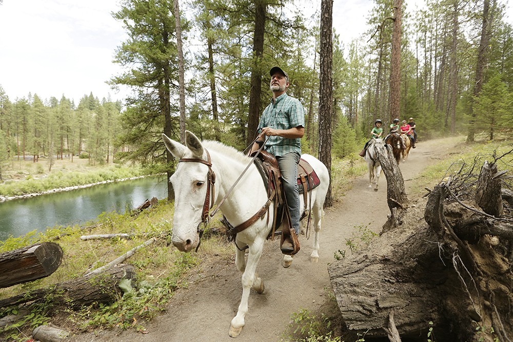 True West Trail Rides co-owner Shawn Anderson, left, leads clients through Riverside State Park in Spokane. - YOUNG KWAK PHOTO