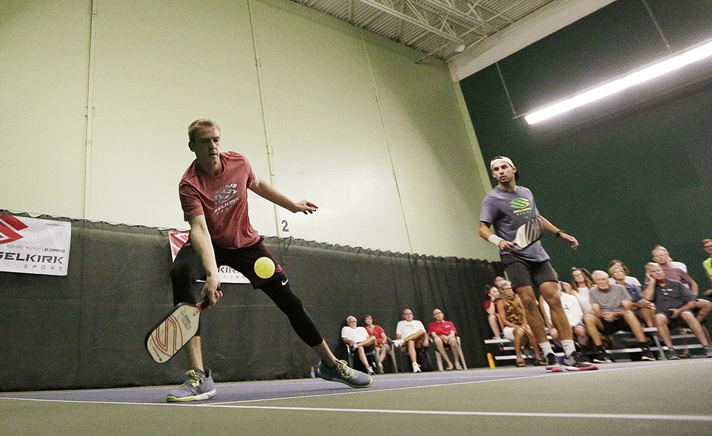 Matt Goebel, left, hits the ball as teammate Tyson McGuffin looks on, during a doubles exhibition match at the North Park Athletic Club. - YOUNG KWAK PHOTO