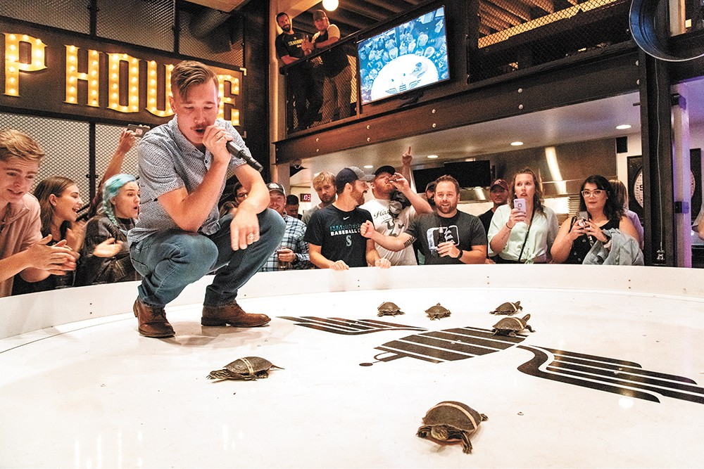 Parker Spady calls the action at Crafted's turtle races. - ERICK DOXEY PHOTO