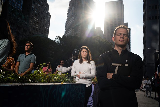 Passersby stop to observe a moment of silence on Dey Street, near the 9/11 Memorial in lower Manhattan, on Thursday, Sept. 11, 2019,  the 18th anniversary of the Sept. 11 terror attacks. - TODD HEISLER/THE NEW YORK TIMES