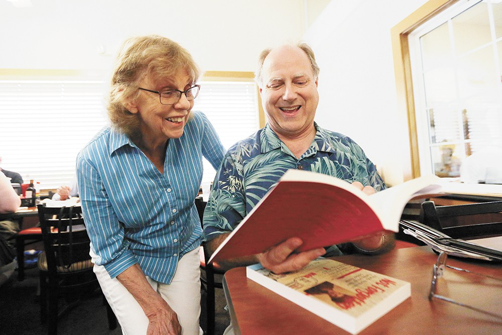 Caryl Briscoe talks to Dave Reynolds about his book during Reynolds' first time attending a Spokane Authors and Self-Publishers meeting. - YOUNG KWAK PHOTO