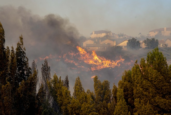 The Saddleridge fire burns in northwest Los Angeles on Friday, Oct. 11, 2019. A fire tore through Southern California overnight into Friday, forcing mandatory evacuations for more than 100,000 people and setting dozens of homes ablaze, just as power was being restored to hundreds of thousands of Northern Californians. - KYLE GRILLOT/THE NEW YORK TIMES