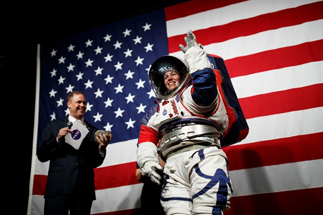 NASA Administrator Jim Bridenstine introduces NASA advance space suit engineer Kristine Davis as she demonstrates the prototype exploration extravehicular mobility unit at NASA Headquarters in Washington on Tuesday, Oct. 15, 2019. The mobility of the suit allowed her to pick a rock and hand it to Bridenstine. - TING SHEN/THE NEW YORK TIMES