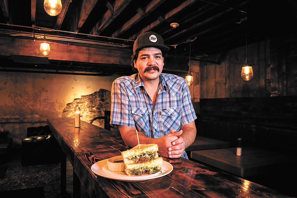 CJ Callahan at Hogwash Whiskey Den with the bar's grilled cheese sandwich. - ERICK DOXEY PHOTO