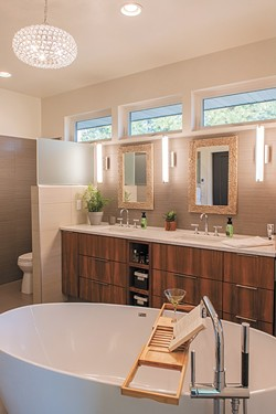 """A soaking tub with views of the treetops lends a """"zen"""" quality to Debbi Bravo's favorite room in her home, the master bath, while the crystal light fixture adds an unexpected sparkle. - ERICK DOXEY PHOTO"""