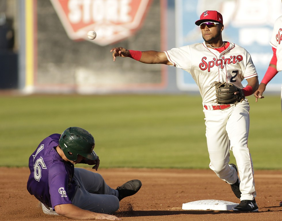 Spokane Indians' Cristian Inoa throws to first, completing double play in a June game. - YOUNG KWAK PHOTO