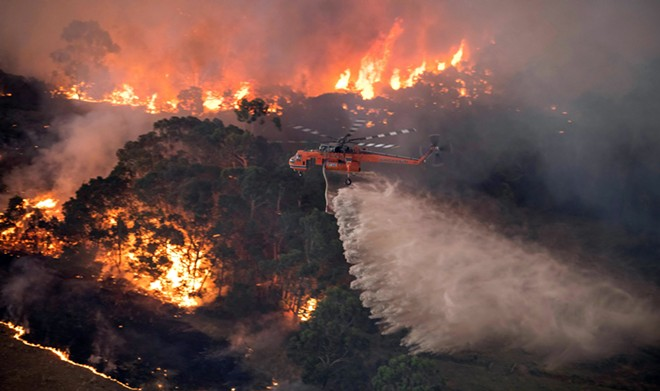 A photo provided by the State Government of Victoria, Australia, shows a helicopter dumping water on a wildfire near Bairnsdale on Tuesday, Dec. 31, 2019.  The country's east coast is dotted with apocalyptic scenes on the last day of the warmest decade on record in Australia. - STATE GOVERNMENT OF VICTORIA VIA THE NEW YORK TIMES