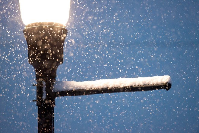 Snow falls around a lampost in the Kendall Yards area. - DANIEL WALTERS PHOTO