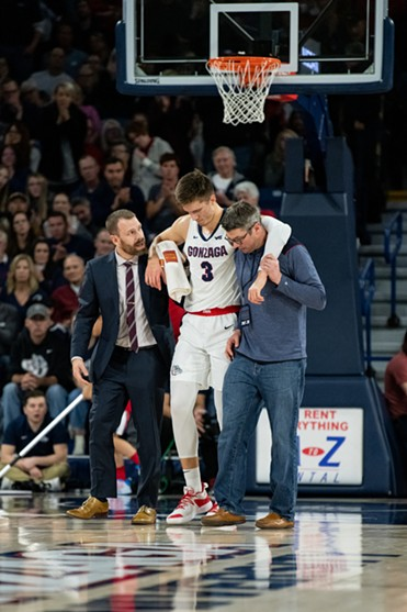 Filip Petruseve is helped off the court. - ERICK DOXEY PHOTO