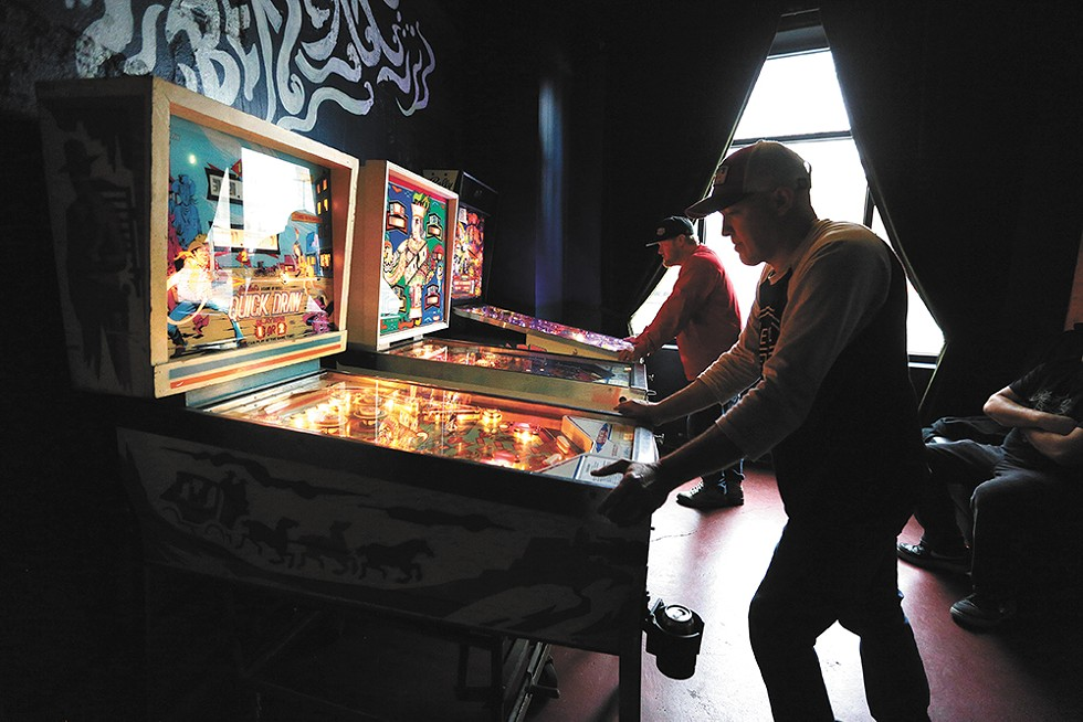Marcus Schmick (left) and Bryce Rich play during a recent tournament for Berserk's pinball league. - YOUNG KWAK PHOTO