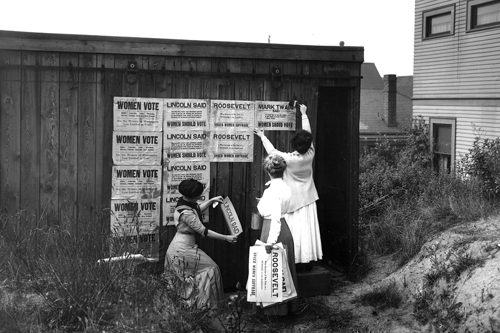 Three women from the Washington Equal Suffrage Association post signs in 1910. - PHOTO BY ASAHEL CURTIS FROM GENERAL SUBJECTS PHOTGRAPH COLLECTION OF THE WASHINGTON STATE ARCHIVES
