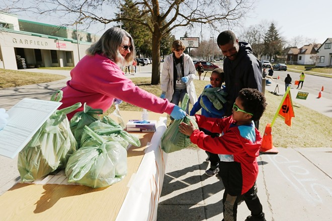 A volunteer hands out a sack of food at Garfield Elementary on Thursday - YOUNG KWAK PHOTO