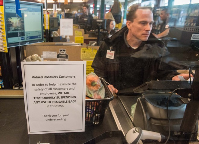 Plexiglas shields Rosauers clerks from sneezing customers, while a sign informs customers that they aren't allowed to bring their own reusable bags. - DANIEL WALTERS PHOTO