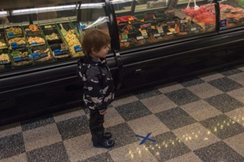 """A very young shopper is enchanted to discover a social-distancing marking """"X"""" has been placed at the meat counter at Rosauers. - DANIEL WALTERS PHOTO"""