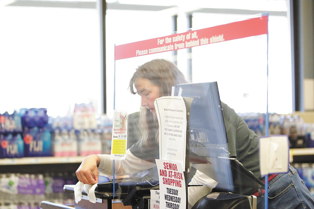Cashier Carla Somerlott cleans a checkout counter at the Rosauers on West 14th Avenue. - YOUNG KWAK PHOTO