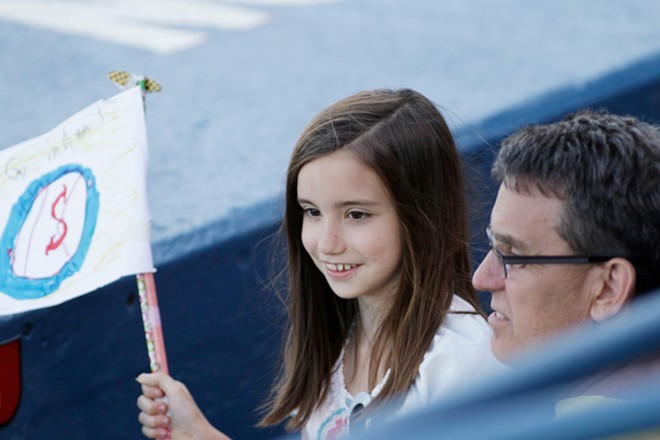 9 year old Eleanor Dinnig, left, holds a homemade Spokane Indians flag while sitting with her father Michael during the third inning. - YOUNG KWAK