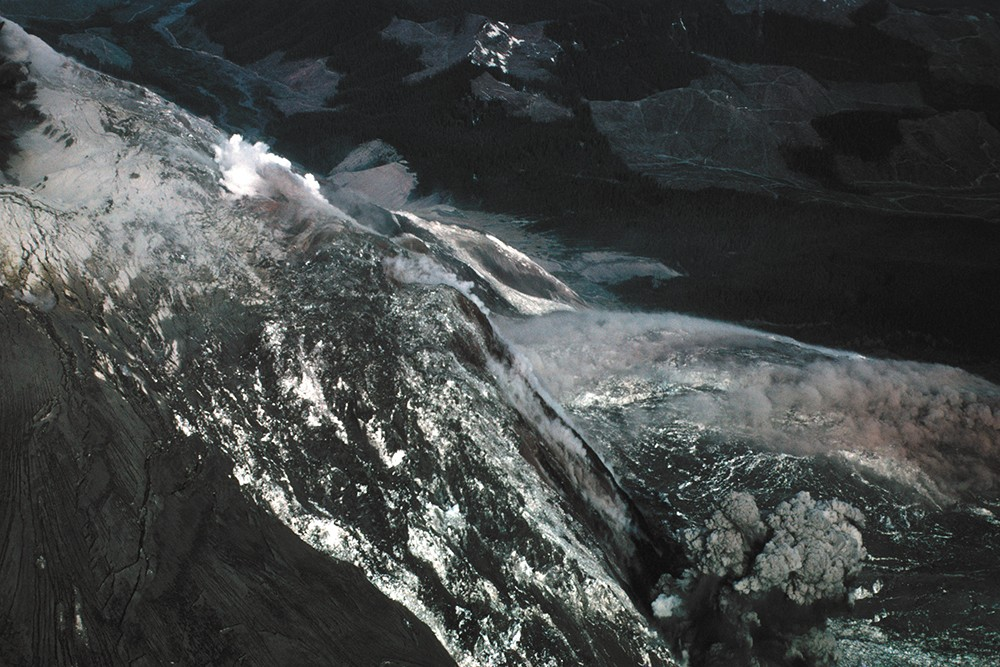 An aerial view as the massive, earthquake-triggered landslide began. The north side of the mountain crumbled away, causing the initial eruptive blast to occur simultaneously out of the volcano's flank and crater. - KEITH AND DOROTHY STOFFEL PHOTO