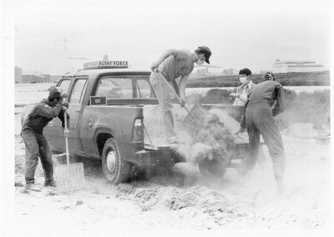 Men unload a truckload of ash during cleanup at Fairchild Air Force Base. - U.S. AIR FORCE