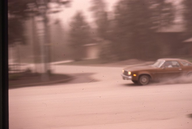 A car travels down an ash-covered residential street on Spokane's South Hill. - COURTESY ROGER CRUM
