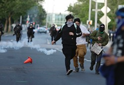 Protesters run as police use tear gas earlier this evening. - YOUNG KWAK PHOTO