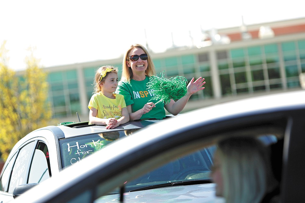 Shadle Park High School counselor Stephanie Filippini, right, and her 6-year-old daughter, Chloe, greet seniors as they arrive to pick up their caps and gowns on May 8 during a drive-up event. - YOUNG KWAK PHOTO