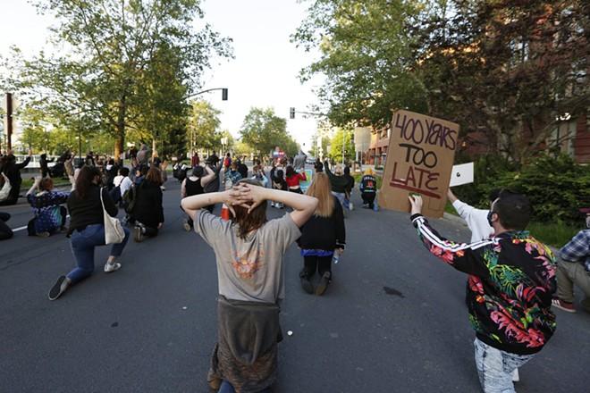 Demonstrators kneel on W. Spokane Falls Blvd., in front of Riverfront Park. - YOUNG KWAK
