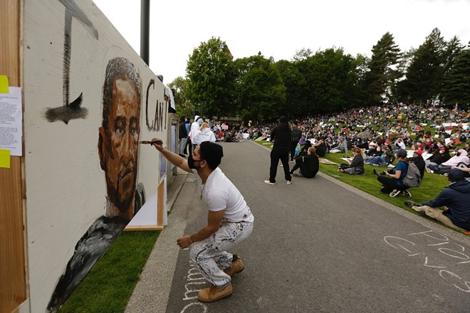 Israel Blackwell painting a portrait of George Floyd. - YOUNG KWAK PHOTO
