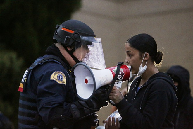 Washington State Patrol Lt. Kris Schweigert, left, speaks with Renee White to help keep the peace with one group of demonstrators in front of the Spokane County Public Works building. - YOUNG KWAK