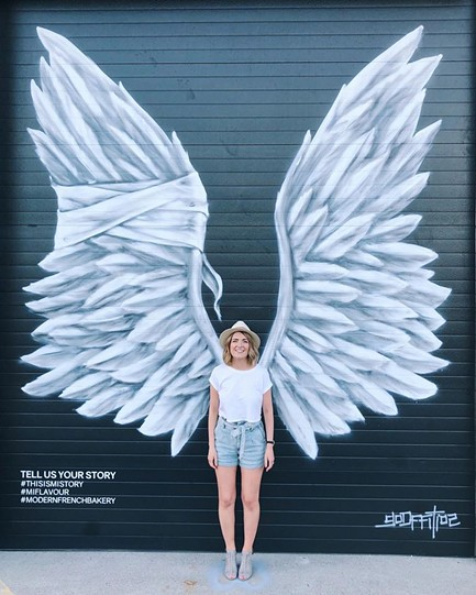 MiFlavour co-owner Ella Piskun stands in front of the bakery's new mural by artist Daniel Lopez. - MIFLAVOUR