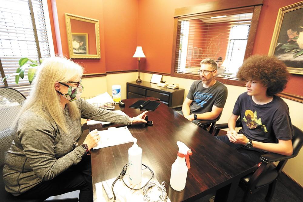 Austin's Fine Jewelry's Rita Everstine hands a ring to customer Matt Kaiser and his son Josiah (right). - YOUNG KWAK PHOTO