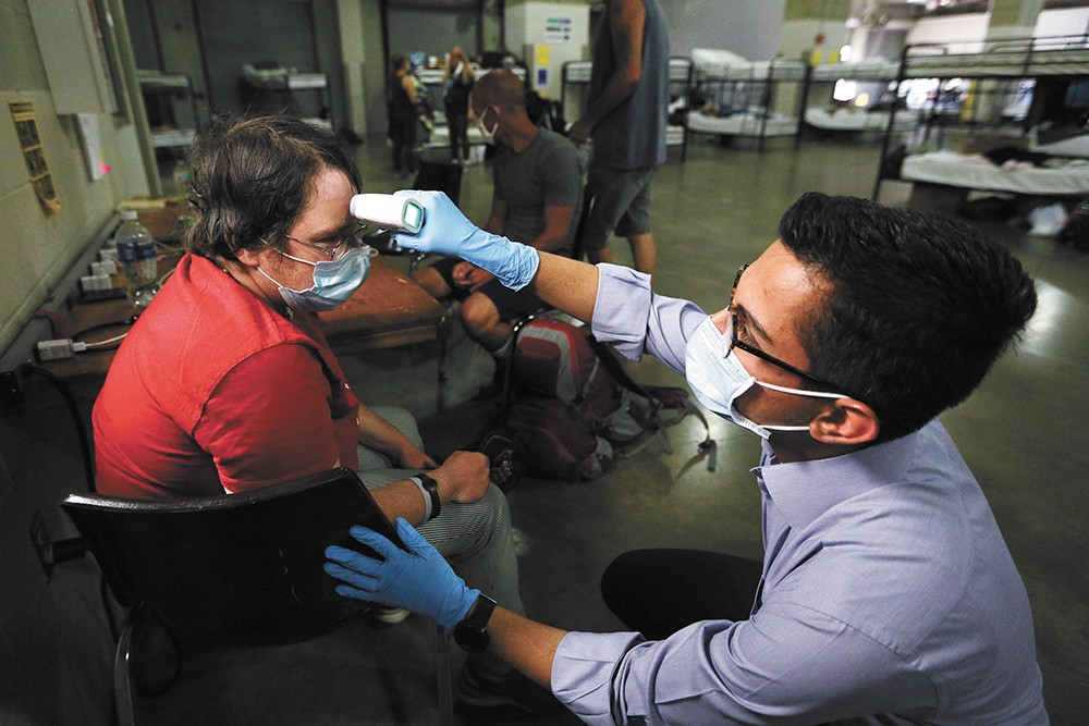 Mohammad Keshtkar checks Amanda Stockton's temperature while conducting a COVID-19 screening at the Spokane Veterans Memorial Arena, which is hosting a temporary shelter for homeless people. - YOUNG KWAK PHOTO