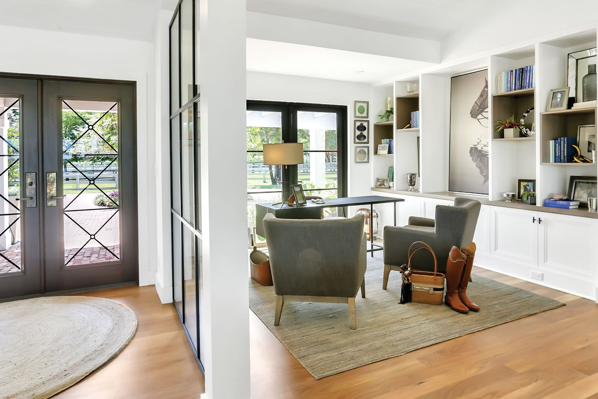 With expansive windows providing views to the stables, this office for a professional equestrian team owner incorporates built-ins to hide office-related equipment, freeing up shelf space for more interesting displays. - PHOTO COURTESY OF DESIGN FOR THE PPL