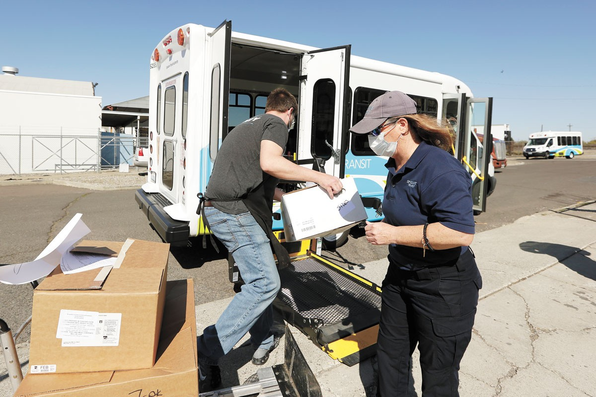 Greater Spokane County Meals on Wheels Kitchen Supervisor Kristopher Elliott-Klemz, left, and STA Paratransit Driver Suzy Paden load frozen meals for delivery. - YOUNG KWAK PHOTO
