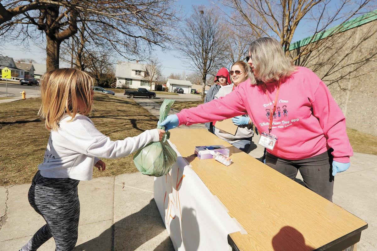 Garfield Elementary Teacher Lonna Gately, right, hands out meals to a student in March. - YOUNG KWAK PHOTO