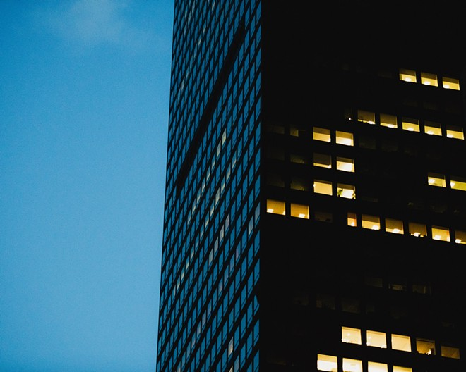 Lights glow at dusk in a few offices of a skyscraper in midtown Manhattan on May 4, 2020. With the coronavirus still surging in some parts of the country, a growing number of employers are delaying return-to-office dates once again, to the summer of 2021 at the earliest. - GEORGE ETHEREDGE/THE NEW YORK TIMES