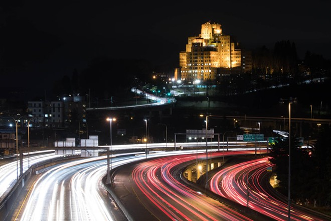 An evening view of the Pacific Tower on Beacon Hill, Seattle, with traffic on Interstate 5 traveling the highway. - MATT M. MCKNIGHT/CROSSCUT PHOTO