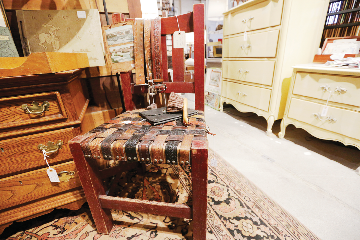 Vintage tooled leather belts find new purpose in this rustic chair on display at Boulevard Mercantile. - YOUNG KWAK PHOTO