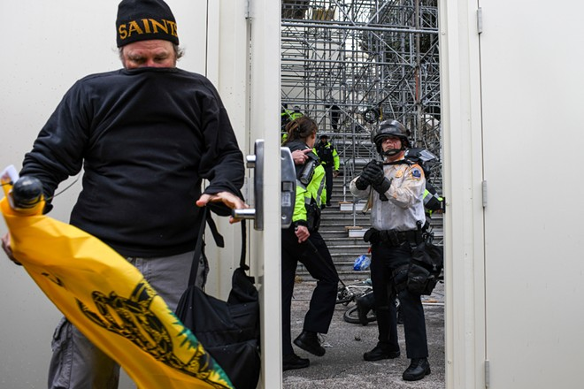 A protester breaches a security door at the Capitol in Washington and is met by police officer, Jan 6, 2020. The Capitol building was placed on lockdown, with senators and members of the House locked inside their chambers, as Congress began debating President-elect Joe Biden's victory. President Trump addressed supporters near the White House before protesters marched to Capitol Hill. - KENNY HOLSTON/THE NEW YORK TIMES