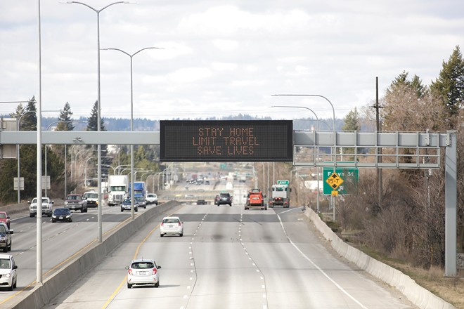"""A sign stating """"stay home, limit travel, save lives"""" is displayed over I-90 in Spokane last March. - YOUNG KWAK PHOTO"""