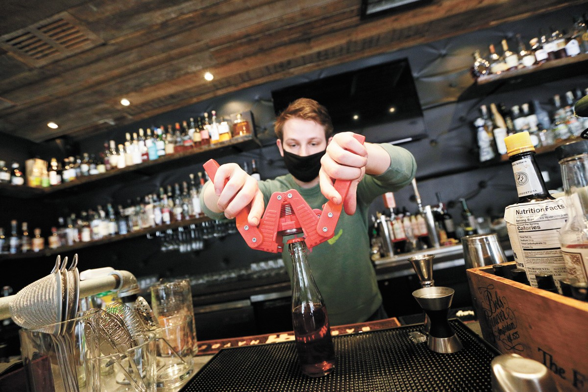 Roman, the general manager at Volstead Act, caps a bottle for a to-go Negroni. - YOUNG KWAK PHOTO