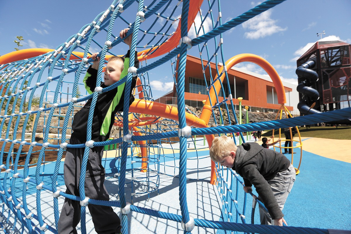 Five-year-olds Malachi Lovoy (left) and Lincoln Gowin climb at the Ice Age Floods Playground during the grand opening of the new North Bank area of Riverfront Park. - YOUNG KWAK PHOTO
