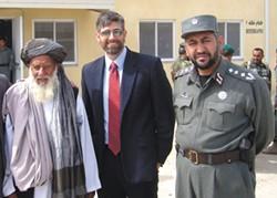 Michael Baumgartner (center) before he was a state senator, flanked by an Afghan elder and police officer. - COURTESY OF ELEANOR BAUMGARTNER