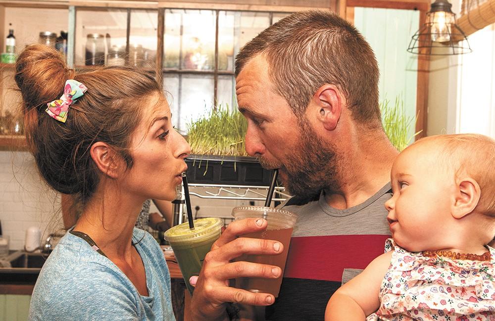 BIJA owner Brandi Elder (left) and John Gardner sip creations from BIJA Organic Juicery and Kombucha Bar as baby Nicoya looks on. - MEGHAN KIRK