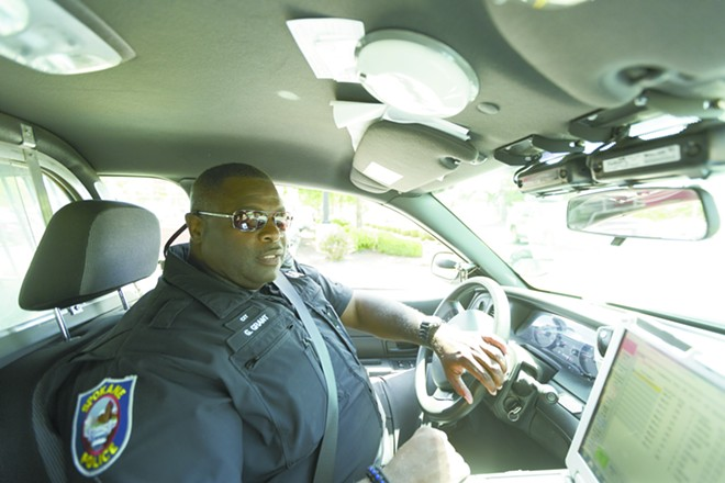 "Officer Gordon Grant in ""baby blue,"" his unmarked patrol car. - YOUNG KWAK PHOTO"
