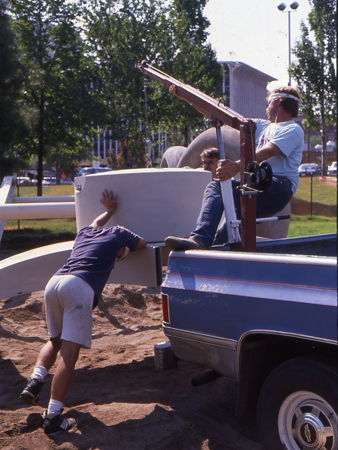 "This slide reads ""1990: Spiering (left) and son Nathan (right) hoisting front yoke into plate on Red Wagon Sculpture."" - PHOTO COURTESY OF KEN SPIERING"
