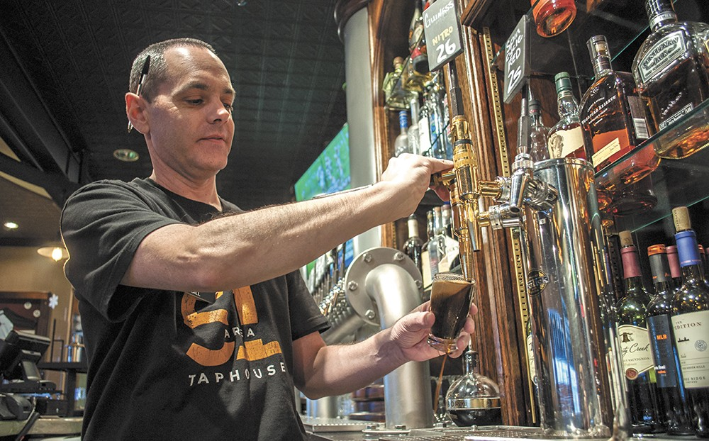 Bill Matthew pours a sample of River City Brewing's Vanilla Burbon Stout at the Area 51 Taphouse. - SARAH WURTZ