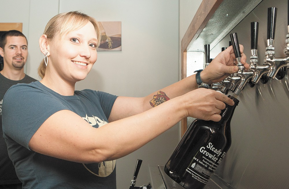 Co-owner Cassaundra Preston pours from one of the 39 taps at Steady Flow Growler House. - MEGHAN KIRK