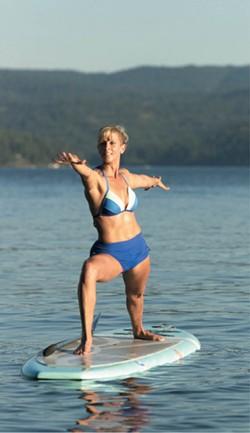 Kim Sherwood demonstrates a warrior pose on Lake Coeur d'Alene. - YOUNG KWAK
