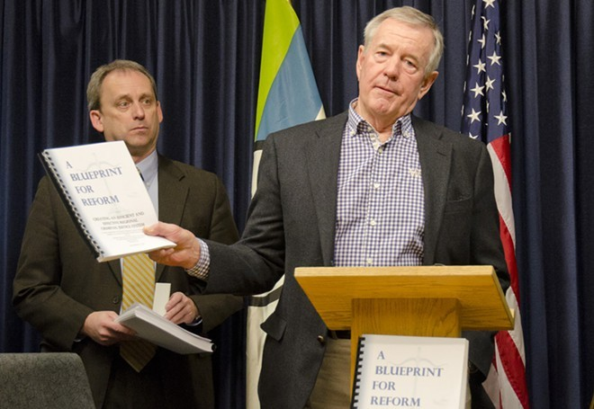 In a 2014 photo, Jim McDevitt holds up the final report from the Spokane Regional Criminal Justice Commission. - JACOB JONES PHOTO